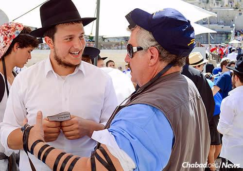Informational brochures are given out at the stand, as well as Shabbat candles and for Chanukah, menorahs. (Photo: Chabad of the Western Wall)