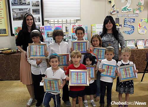 Hebrew-school class for young families during the year, and in the summer, Camp Gan Israel is offered. Chabad emissary Rachel Zarchi stands at left.