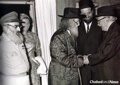 Shazar, right, and Rabbi Dovid Cohen greet each other as Rabbi She'ar Yashuv Cohen looks on. To the far left is Rabbi Shlomo and Tzefiya Goren, Rabbi She'ar Yashuv's brother-in-law and sister.