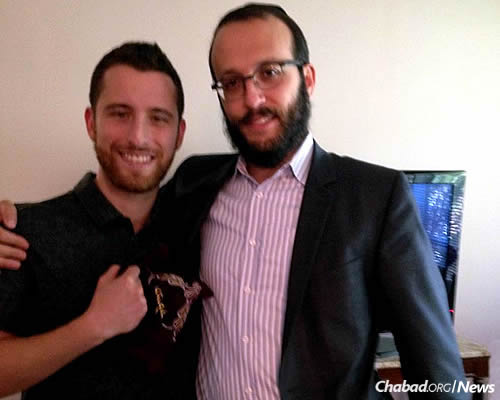 Dustin, left, the son of a man named Aubie who was visited by Rabbi Levi Gansburg, right, co-director of Chabad Lubavitch of York Mills in Toronto, Canada, holds tefillin wrapped by his father. They were given to him as a gift soon after his father passed away.