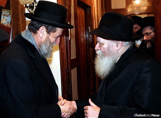 Rabbi She'ar Yashuv Cohen, left, chief rabbi of Haifa for 36 years, during one of many visits with the Lubavitcher Rebbe in the Crown Heights neighborhood of Brooklyn, N.Y. Here, he is at a Sunday dollars distribution in 1991. (Photo: JEM/The Living Archive)