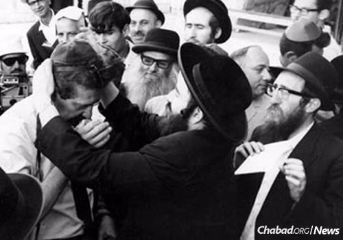 Ezer Weizman, left, wraps tefillin at the Kotel; he would become president of Israel in 1993 and 1998.