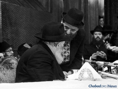 Cohen speaks with the Rebbe at a farbrengen. (Photo: JEM/The Living Archive)