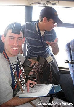 Laible Schmidt on an airplane back from a Birthright Israel trip for adults with special needs. Here, he helps his seatmate don tefillin and recite the Shema.