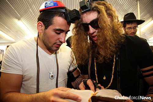 Many students are introduced to tefillin and have the opportunity to don them, assisted by rabbis and oftentimes their own peers. (Photo: Chabad on Campus International)