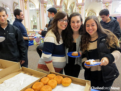 Chasi Rothstein with Pitt students Haley Platt, center, and Jamie Barishman at a Chanukah festival on campus (jelly doughnuts included).