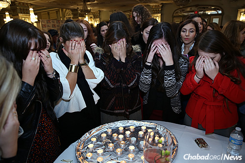 Reciting prayers over candles before Shabbat (Photo: Chabad on Campus International)