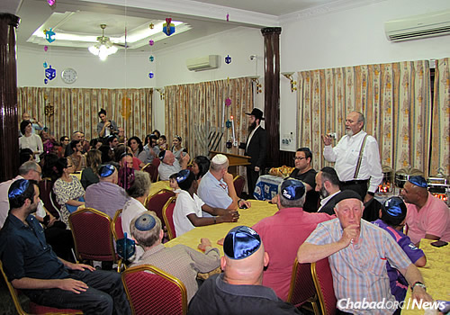 The rabbi begins to light the menorah at a Chanukah party.