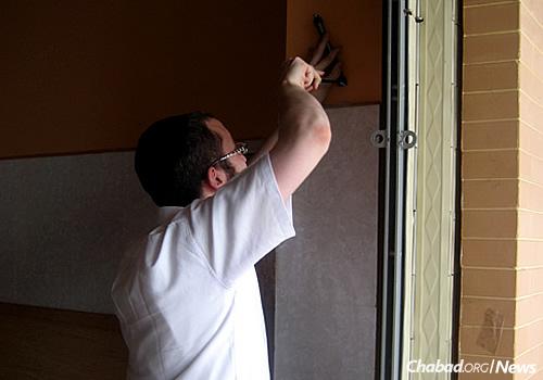Rabbi Butman hangs a mezuzah on the door of the new Chabad building.