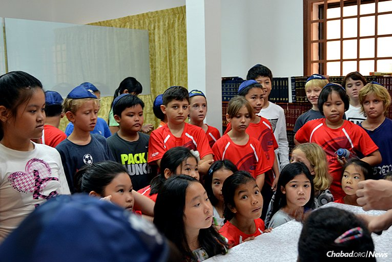 Children in Cambodia's capital city of Phnom Penh are shown a model Torah scroll. They are gathered at the Chabad Jewish Center, directed by Rabbi Bentzion and Mashie Butman.