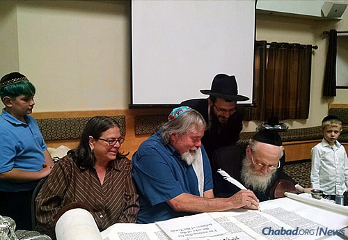 The Sillen family writes Hebrew letters with Klein; Rabbi Chaim Zaklos, co-director of Chabad-Lubavitch of Solano County, observes behind them.