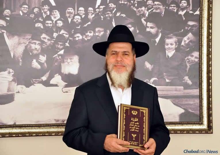 Rabbi YomTov Hakohen Guindi holds the first edition of his modern rendering of Rabbi Saadia Gaon's Arabic-language Tafsir.