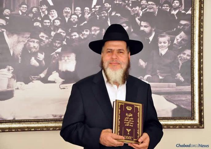 Rabbi YomTov Hakohen Guindi holds the first edition of his modern rendering of Rabbi Saadia Gaon's Arabic-language Tafsir.