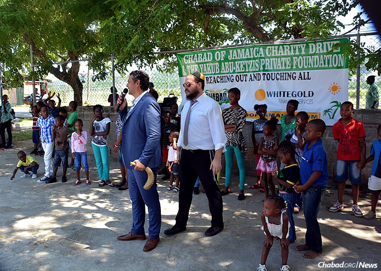A Family Fun Day in Jamaica, sponsored by Chabad of Jamaica and the Yakub Abu-Ketzis Private Foundation, was just one part of larger efforts geared towards assisting the local population. Some 200 children received free school supplies at the Sunday event. Here, the crowd gets to hear the sounding of the shofar in the midst of the Jewish High Holiday season.