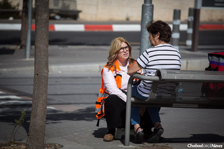 A volunteer social worker from the Magen David Adom emergency medical services comforts a woman who witnessed a terrorist attack while waiting for a train at a light-rail stop in Jerusalem. (Photo: Hadas Parush/Flash90)