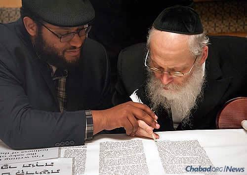Local supporter Andrew Wise, left, writes a letter in the community's new Sefer Torah, assisted by the scribe, Rabbi Moshe Klein.