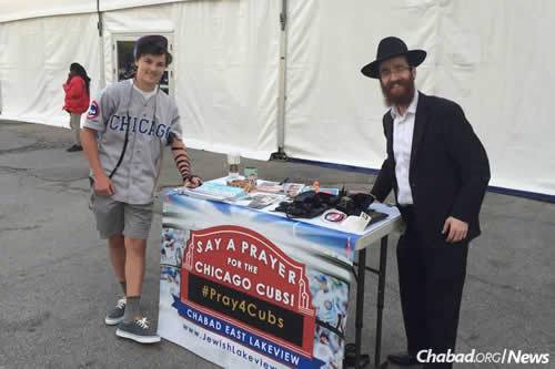Rabbi Dovid Kotlarsky, right, has been stationing himself around Wrigley Field with tefillin, encouraging Jewish baseball fans to wrap the traditional leather prayer straps.