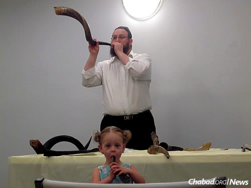 Checking out shofars prior to Rosh Hashanah at a Shofar Factory Workshop. The rabbi gets a little help from a little participant.