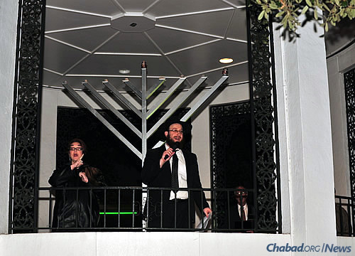 "The rabbi at the event; to his left is an American Sgn Language interpreter. To his right is Mayor Sandy Stimpson, who lit the shamash (""helper candle"") on the 9-foot menorah."