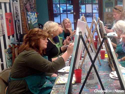 "Women work on art a ""paint night"" activity prior to Shavuot."