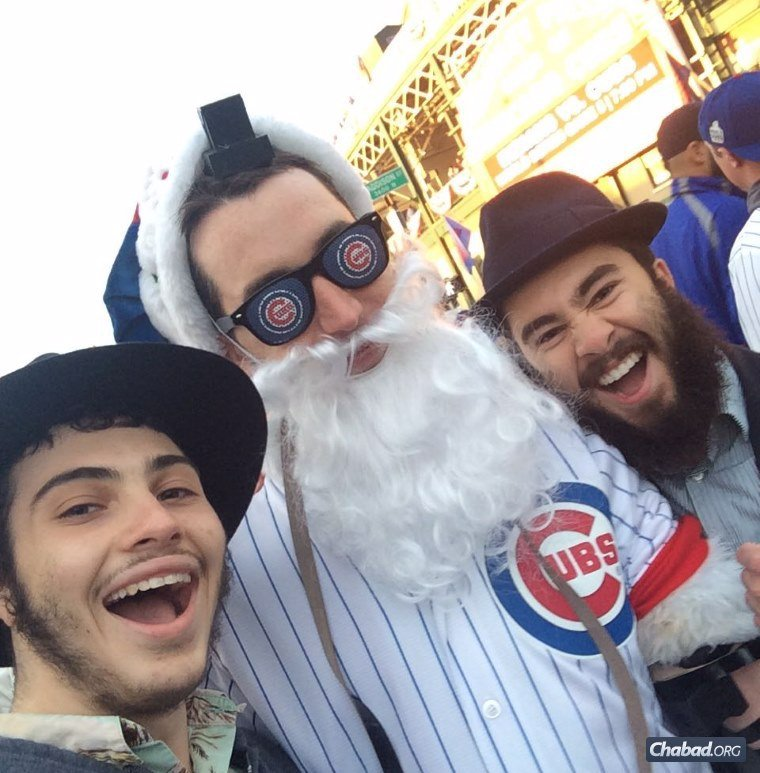 Skokie CTeen members David Goldshmidt and Noah Wasserman help a happy Cubs' fan into tefillin.