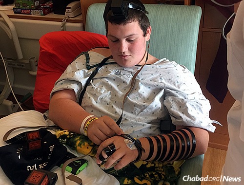 Wrapping tefillin in the hospital, where he has been in and out of for years.