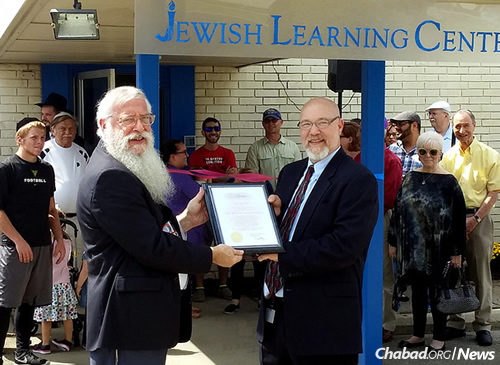 The new Jewish Learning Center, or JLC, will offer classes for all ages with a stress on evening adult education. Rabbi Avrohom Litvin, left, regional head Chabad-Lubavitch emissary and co-director of Chabad of Kentucky, accepts a certificate from the mayor's office on the center's opening.