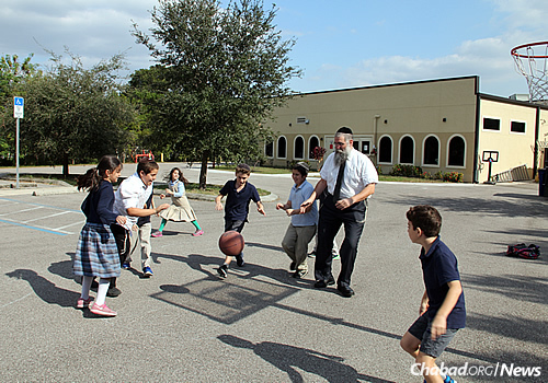 Girls and boys play basketball on the school recreation area.