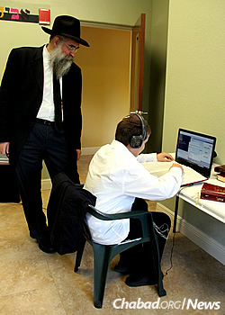 The rabbi looks on as Yehoshua Greenberg studies in the computer library.
