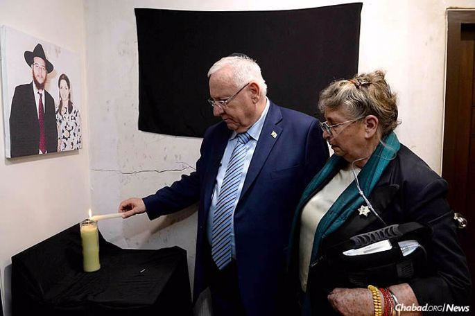 Israeli President Reuven Rivlin visited the Chabad House in Mumbai, India, on Nov. 20, marking eight years since the terrorist attack that murdered Rabbi Gavriel and Rivka Holtzberg, four of their guests and 158 others throughout the city. The Chabad House was reopened two years ago, and is led today by Rabbi Yisroel and Chaya Kozlovsky. Here, Rivlin and his wife, Nechama, light a memorial candle at the Chabad House in front of a photo of the Holtzbergs. (Photo: Chabad of Mumbai)