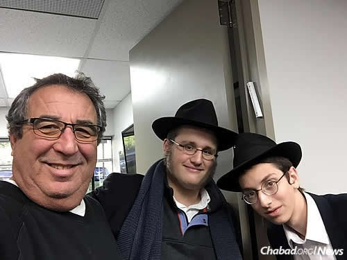 Mendel Azimov and Mendel Zaklikovsky put up a mezuzah on an office doorpost. They also make time to chat, answer questions and pose for a photo or two.