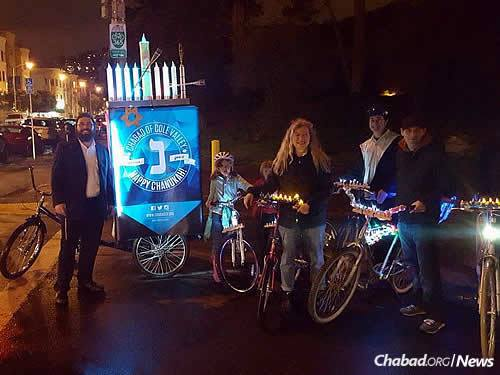 Rabbi Nosson Potash, left, co-director of Chabad of Cole Valley in San Francisco, at a previous bike-menorah parade. A fan of WhatsApp, he is employing such tools to publicize this year's ride on Dec. 29, followed by a menorah-lighting.