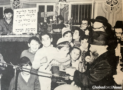 Rabbi Henich Rapoport, right, pictured here with immigrant children in Israel, hosted famed 19 Kislev farbrengens at his home in Moscow during dangerous times.