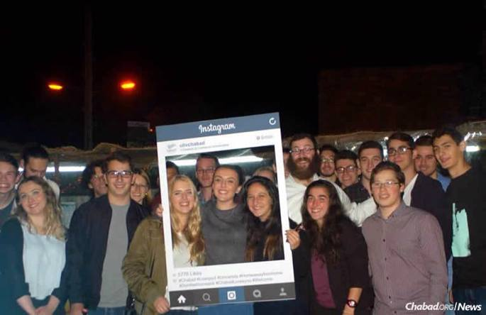 Rabbi Shmuli Brown, to the right of the picture frame, who co-directs Chabad at Liverpool Universities in England, is using social media to connect with students over Chanukah. He's posting links to public menorah-lightings in London and running nightly competitions, entering those who post and tag pictures of themselves lighting menorahs on Facebook, Instagram and Twitter for a chance to win raffle prizes.