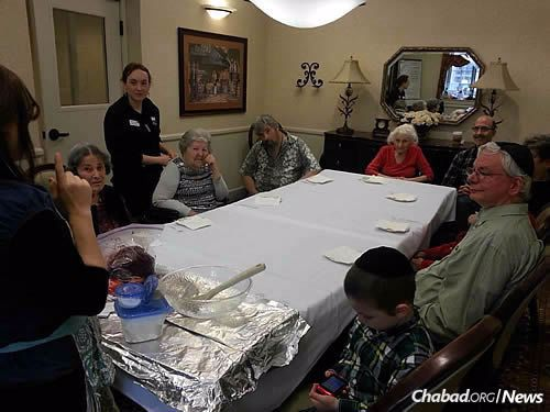Chaya Potash, left, co-director of Chabad of Cole Valley in San Francisco, talks to seniors about latke-making at Chanukah time. The goal is to meet people where they are, often connecting through technology and then meeting in person.