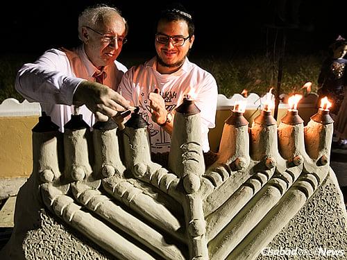 Community member Leslie Evans, left, lit the sand menorah in Palm Beach.