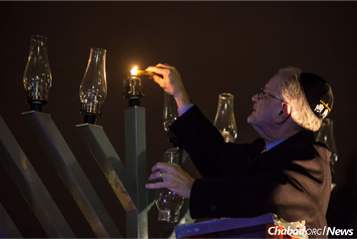 Former Gallaudet President Dr. T. Alan Hurwitz lights the shamash candle at the first public menorah-lighting ceremony (2013) at Gallaudet University in Washington, D.C. (Photo: Emily Cohen)