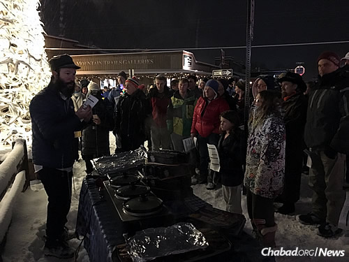 Rabbi Zalman Mendelsohn, co-director of Chabad-Lubavitch of Wyoming, offers hot food on a cold night at a Chanukah menorah-lighting in Jackson Hole.