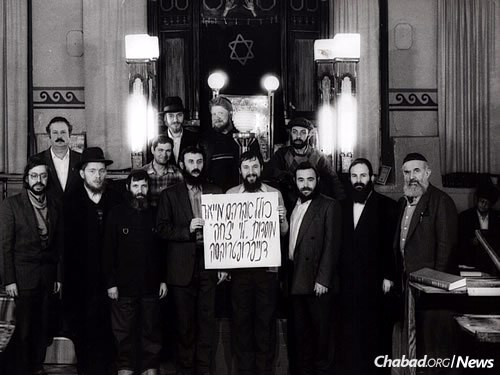 "Members of the ""Kollel Avraham Mayor"" pose in front of the ark in the old synagogue in Dnepropetrovsk in the early 1990s."
