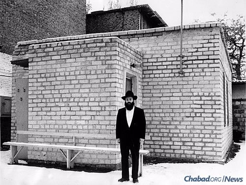 Success came slowly in the beginning, and a mikvah was one of them. Kaminezki stands in front of Dnepropetrovsk's then-new mikvah in the early 1990s.