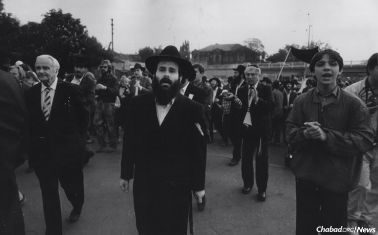 This month marks 25 years since the fall of the Soviet Union in December 1991. Permanent Chabad-Lubavitch emissaries first arrived in Moscow, Dnepropetrovsk and Kharkov a year earlier, where they were greeted by hundreds of thousands of spiritually thirsting Jews. Here, Rabbi Shmuel Kaminezki, center, leads a Torah completion ceremony in the city of Dnepropetrovsk, circa 1991.
