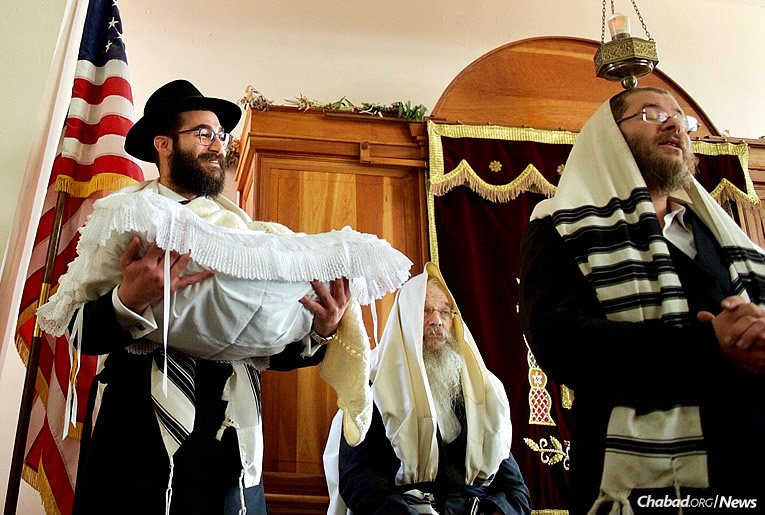 Rabbi Yehuda Ceitlin, left, outreach director for Chabad Lubavitch of Tucson, holds his son at the bris on Monday. His wife, Feigie Ceitlin, program director for the Chabad center, gave birth on Dec. 25, right after the couple's main Chanukah event. (Photo: Britta Van Vranken)