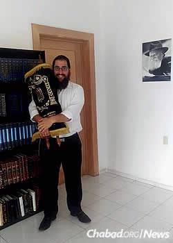Rabbi Shneur Hecht holds their Torah