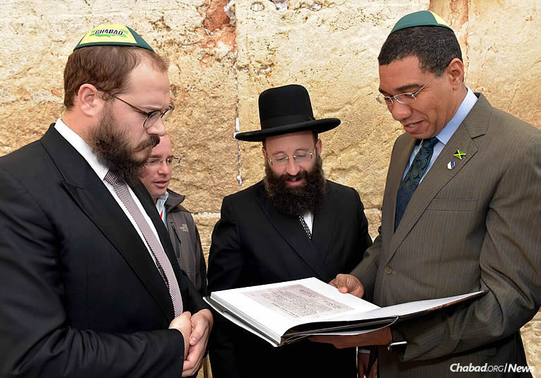 Prime Minister of Jamaica Andrew Holness, right, visited Israel to discuss mutual concerns with Prime Minister Benjamin Netanyahu. Here, he is accompanied to the Western Wall (Kotel) in Jerusalem by Rabbi Yaakov Raskin, left, co-director of Chabad of Jamaica. In the center is Rabbi Shmuel Rabinowitz, rabbi of the Western Wall.