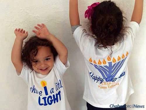 "Menachem, 2, and Tzivi Hecht, 3, don Chanukah T-shirts that read: ""Share a Little Light."""