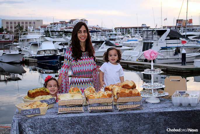 Mushkie Hecht, co-director of Chabad of Puerto Vallarta, and her two young children sell loaves of challah, with all kinds of seasonings, at the farmers market by the city's marina. She says it's a great way to meet local residents and tourists.