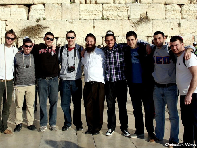 """The Durham-Chapel Hill Jewish Federation chose to honor Rabbi Zalman and Yehudis Bluming, co-directors of the Rohr Chabad of UNC Chapel Hill and Duke University, with the Earl & Gladys Siegel Young Leadership Award. Here, the rabbi accompanies a group of college students to the Western Wall (Kotel) in Jerusalem as part of an """"Israelinks"""" Chabad on Campus trip."""