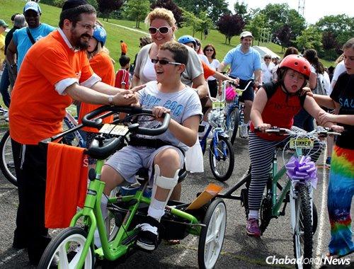 Volfman got his first custom bike at age 12, thanks to a project called Olivia's Friendship Cycle. To his left is Rabbi Zalman Grossbaum of Friendship Circle New Jersey.