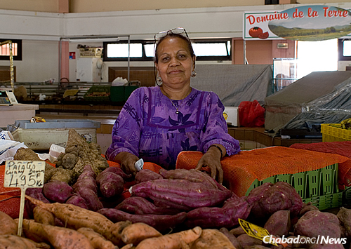 A woman sells sweet potatoes at the fruit market in Nouméa. (Photo: Wikimedia Commons)