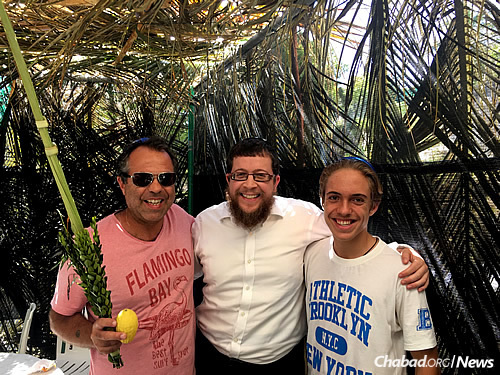 Haim David Helias, left, and his son, Abel, join the rabbi in the sukkah.